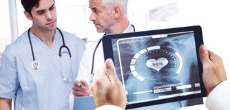 Composite image of man using tablet pc. Man using tablet pc against doctors talking about a file Stock Photos