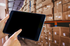 Composite image of man using tablet pc. Man using tablet pc against forklift in large warehouse Royalty Free Stock Image