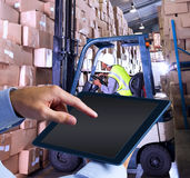 Composite image of man using tablet pc. Man using tablet pc  against forklift machine in warehouse Stock Photos