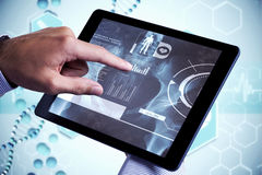 Composite image of man using tablet pc. Man using tablet pc against medical icons in blue and white stock photos