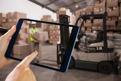 Composite image of man using tablet pc. Man using tablet pc against warehouse worker loading up pallet Stock Images