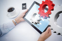 Composite image of man using tablet pc. Man using tablet pc against white and red cogs and wheels Royalty Free Stock Image