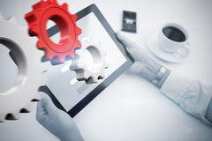 Composite image of man using tablet pc. Man using tablet pc against white and red cogs and wheels Stock Photos