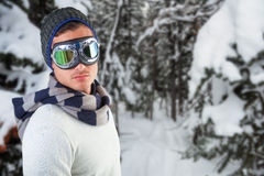 Composite image of man wearing aviator goggles against white background. Man wearing aviator goggles against white background against snow covered pine trees on royalty free stock image