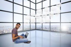 Composite image of man wearing glasses sitting on floor using laptop and looking at camera Stock Images