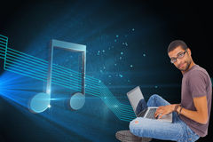 Composite image of man wearing glasses using laptop and looking at camera Stock Photography