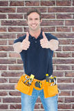 Composite image of man wearing tool belt while showing thumbs up sign Stock Image