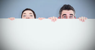 Composite image of man and woman hiding behind a white board with room for  copy space. Man and women hiding behind a white board with room for  copy space Stock Photography