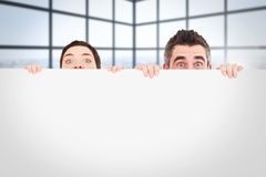 Composite image of man and woman hiding behind a white board with room for  copy space Stock Photo