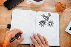 Composite image of man writing notes on diary Royalty Free Stock Photos