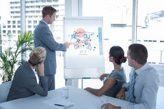 Composite image of manager presenting whiteboard to his colleagues. Manager presenting whiteboard to his colleagues against global business interface Royalty Free Stock Photography
