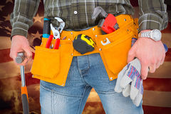 Composite image of manual worker holding gloves and hammer. Manual worker holding gloves and hammer against composite image of digitally generated united states Royalty Free Stock Images