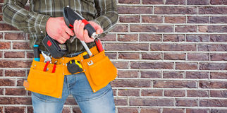 Composite image of manual worker holding gloves and hammer power drill. Manual worker holding gloves and hammer power drill against red brick wall royalty free stock images