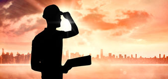 Composite image of manual worker wearing hardhat while holding clipboard Stock Photography