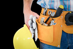 Composite image of manual worker wearing tool belt while holding gloves and helmet. Manual worker wearing tool belt while holding gloves and helmet against black stock images