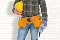 Composite image of manual worker wearing tool belt while holding gloves and helmet Stock Photography