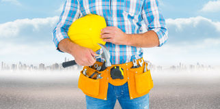 Composite image of manual worker wearing tool belt while holding hammer and helmet Stock Photos