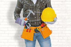 Composite image of manual worker wearing tool belt while holding hammer and helmet Royalty Free Stock Photos