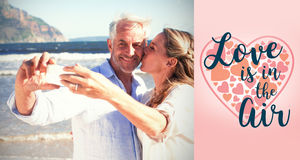 Composite image of married couple at the beach together taking a selfie. Married couple at the beach together taking a selfie against backgrounds working Stock Photos