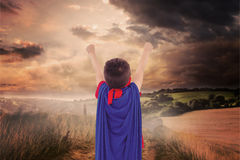 Composite image of masked boy pretending to be superhero. Masked boy pretending to be superhero against country scene Royalty Free Stock Images