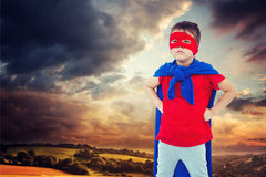 Composite image of masked boy pretending to be superhero. Masked boy pretending to be superhero against country scene Royalty Free Stock Photo