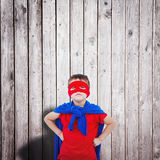 Composite image of masked boy pretending to be superhero. Masked boy pretending to be superhero against digitally generated grey wooden planks Stock Image