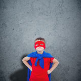 Composite image of masked boy pretending to be superhero. Masked boy pretending to be superhero against dirty old wall background Royalty Free Stock Images
