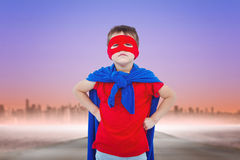 Composite image of masked boy pretending to be superhero. Masked boy pretending to be superhero against fog covered street leading towards skyline Stock Image