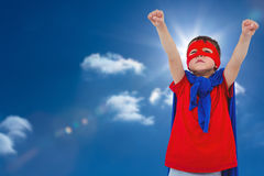 Composite image of masked boy pretending to be superhero. Masked boy pretending to be superhero against sky with sun Royalty Free Stock Images