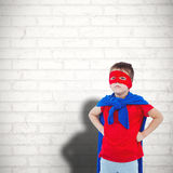 Composite image of masked boy pretending to be superhero. Masked boy pretending to be superhero against white wall Royalty Free Stock Photography
