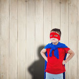 Composite image of masked boy pretending to be superhero. Masked boy pretending to be superhero against wooden planks Royalty Free Stock Images