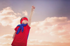 Composite image of masked boy pretending to be superhero on white screen. Masked boy pretending to be superhero on white screen against beautiful blue cloudy sky Royalty Free Stock Photos