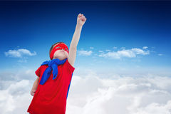 Composite image of masked boy pretending to be superhero on white screen. Masked boy pretending to be superhero on white screen against bright blue sky over Stock Images
