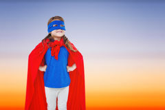 Composite image of masked girl pretending to be superhero. Masked girl pretending to be superhero against beautiful orange and blue sky Royalty Free Stock Photos