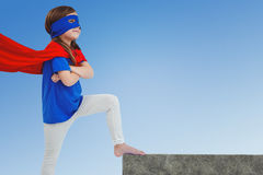 Composite image of masked girl pretending to be superhero Royalty Free Stock Photo