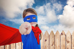 Composite image of masked girl pretending to be superhero Royalty Free Stock Photography