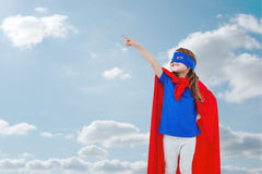 Composite image of masked girl pretending to be superhero Stock Image