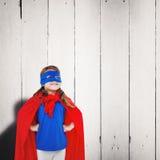 Composite image of masked girl pretending to be superhero Stock Photo