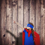 Composite image of masked girl pretending to be superhero Royalty Free Stock Photos