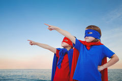 Composite image of masked kids pretending to be superheroes. Masked kids pretending to be superheroes against beautiful sunset on a sunny day Stock Image