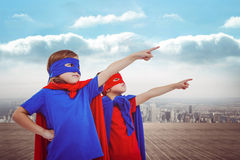 Composite image of masked kids pretending to be superheroes. Masked kids pretending to be superheroes against city on the horizon Stock Photo