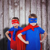 Composite image of masked kids pretending to be superheroes. Masked kids pretending to be superheroes against digitally generated grey wooden planks Stock Image
