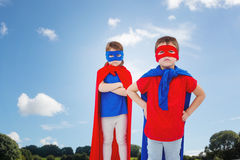 Composite image of masked kids pretending to be superheroes. Masked kids pretending to be superheroes against green field Stock Photography