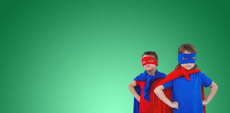 Composite image of masked kids pretending to be superheroes. Masked kids pretending to be superheroes against green vignette Royalty Free Stock Images