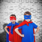 Composite image of masked kids pretending to be superheroes. Masked kids pretending to be superheroes against grey brick wall Stock Photography