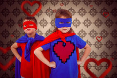 Composite image of masked kids pretending to be superheroes. Masked kids pretending to be superheroes against love heart pattern Royalty Free Stock Images