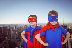 Composite image of masked kids pretending to be superheroes. Masked kids pretending to be superheroes against new york skyline Royalty Free Stock Images