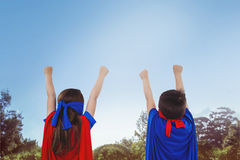 Composite image of masked kids pretending to be superheroes. Masked kids pretending to be superheroes against park on sunny day Stock Photo