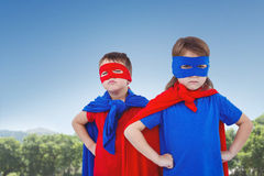 Composite image of masked kids pretending to be superheroes. Masked kids pretending to be superheroes against park on sunny day Royalty Free Stock Photos
