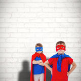 Composite image of masked kids pretending to be superheroes. Masked kids pretending to be superheroes against white wall Stock Photo